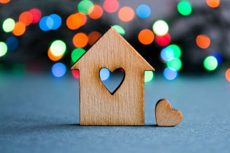 family home: Wooden house with hole in the form of heart with little heart on colorful bokeh background. Stock Photo