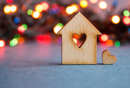 Wooden house with hole in the form of heart with little heart on colorful bokeh background. Stock Photo