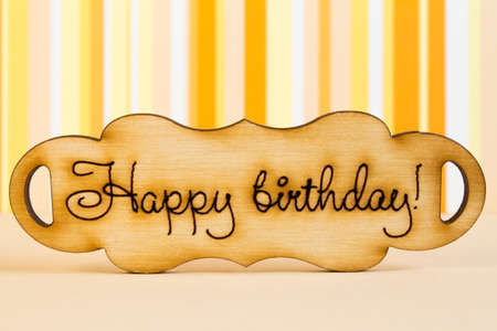italics: Wooden plaque with the inscription Happy Birthday on orange striped background. Stock Photo