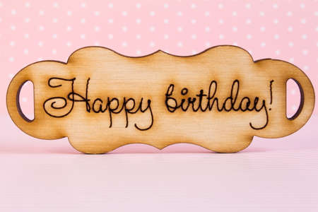 italics: Wooden plaque with the inscription Happy Birthday on pink background.