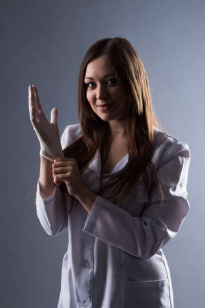 medical light: Female beautiful doctor wear rubber medical gloves in contrasting light.