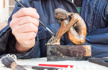 sculptor: Hands of sculptor hold sculpture and clean it with brush.