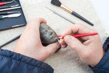 Hands of sculptor making sculpture head using instruments. photo