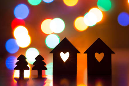 silhouette maison: Silhouette de deux maisons avec un trou en forme de coeur avec deux petits arbres de noël et avec des lumières de guirlande sur le fond. Banque d'images