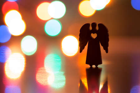 religious angel: Silhouette of Christmas angel with hole in form of heart with garland lights on background.