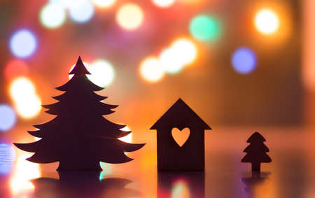 Silhouette of house with hole in form of heart and two Christmas trees with garland lights on backgrounds Stock Photo