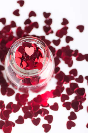 full filled: Open glass jar filled with many red little hearts on white background.