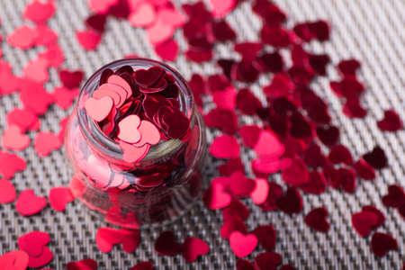 full filled: Open glass jar filled with many red little hearts. Stock Photo