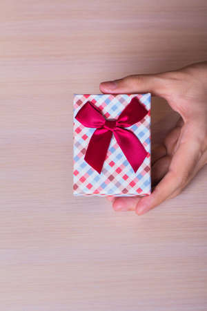 vinous: One male hand holding checkered gift box with vinous bow vertical