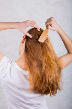 combing: Red-haired young woman combing hair with wooden comb.