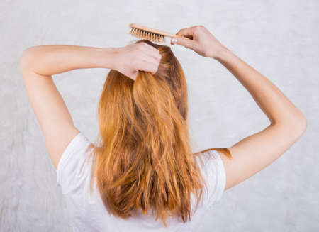 comb hair: Red-haired young woman combing hair with wooden comb.