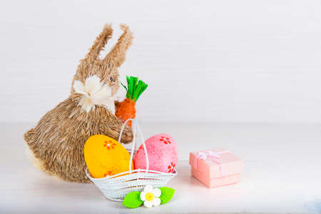 white eggs: Wicker Easter bunny with Easter eggs in basket on white wooden background and pink gift box Stock Photo