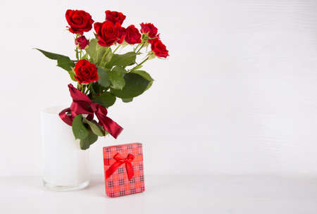 Bouquet of red roses with red gift box on white background. Stock Photo