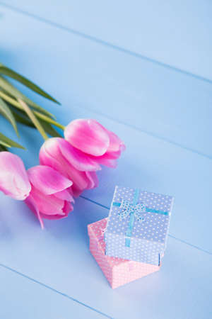 Bouquet of tender pink tulips with two gift boxes on light blue wooden background