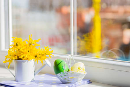 Colored easter egg and white little can with yellow flowers near window.