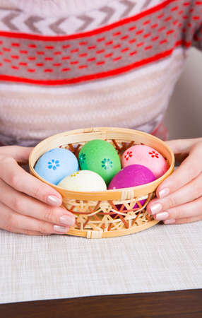 Female hands holding wicker basket with colored easter eggs.
