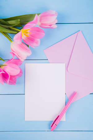 Bouquet of tender pink tulips with empty paper sheet and envelope on blue wooden background Stock Photo
