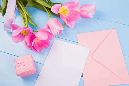 Bouquet of tender pink tulips with empty paper sheet, envelope and gift box on blue wooden background