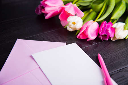 Beautiful bouquet of tender pink and white tulips, envelope, pen and clear paper sheet on black wooden background. Spring romantic composition.