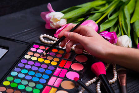 Female hands holding cosmetic brush with eyeshadow palette and beautiful bouquet of tender pink and white tulips and pearls on black wooden background. Spring romantic composition.