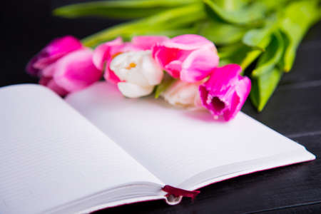 Beautiful bouquet of tender pink and white tulips and open notebook on black wooden background. Spring romantic composition.