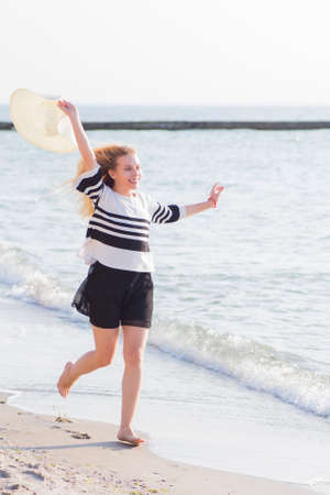 Beautiful young blond-haired girl smiling and running on seaside at morning. Stock Photo