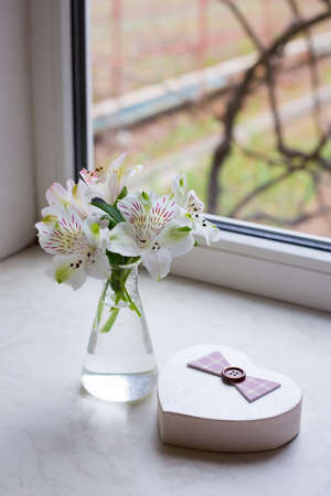 Beautiful tender bouquet of white Alstroemeria in glass vase with gift box in shape of heart near window. Spring composition. Springtime. Mother`s day card.