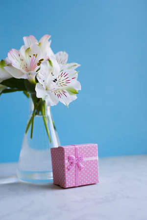 Beautiful tender bouquet of white Alstroemeria in glass vase with pink gift box on blue background. Spring composition. Springtime. Mother`s day card.