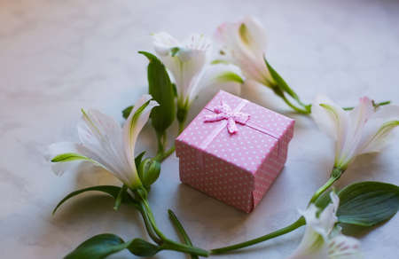 Pink gift box surrounded with alstroemeria flowers on marble surface. Spring composition. Springtime. Mother`s day card.