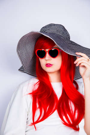 Attractive red-haired young woman in sunglasses in form of heart and striped white and black hat on white background. Sexy stylish model enjoying sun. Summertime.