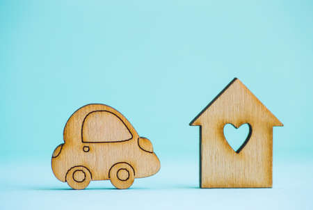 Wooden house with hole in form of heart with wooden car icon on mint background. Concept of moving. Symbol of traveling.
