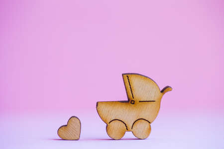 Wooden icon of baby buggy and little heart on pink background. Sign of baby carriage. Symbol of childbirth. Stock Photo