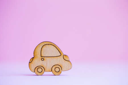 Wooden car icon on light pink background. Concept of moving. Symbol of traveling. Stock Photo
