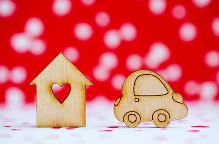 Wooden house with hole in form of heart with wooden car icon on red and white background. Concept of moving. Symbol of traveling.