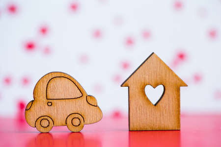 Wooden house with hole in form of heart with wooden car icon on pink and white background. Concept of moving. Symbol of traveling.