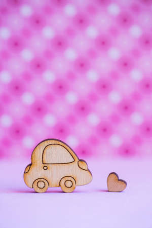 Wooden car icon with little heart on pink spotted background. Concept of romantic trip. Symbol of traveling. Stock Photo