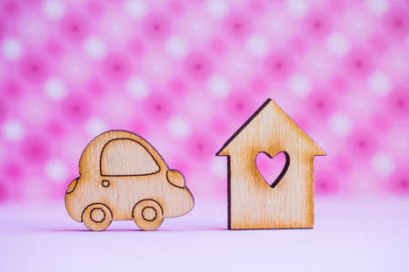 Wooden house with hole in form of heart with wooden car icon on pink spotted background. Concept of moving. Symbol of traveling.