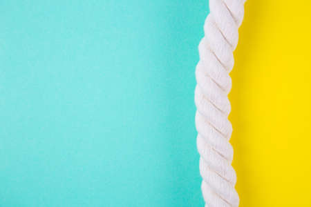 Sea rope on colored mint green and yellow backgrounds with negative space. Minimalistic colorful summer background. Top view. Flat lay in marine style.
