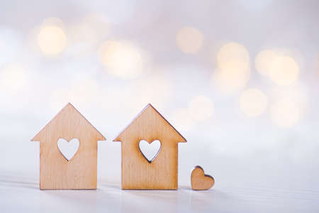 Two wooden houses with hole in the form of heart with little heart on light bokeh background. Romantic card. Concept of sweet home. Stock Photo