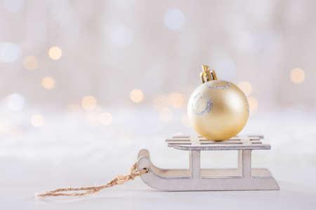 Bola brillante de la Navidad en el trineo blanco del juguete en fondo ligero del bokeh. Tarjeta de año nuevo. Decoración de Navidad