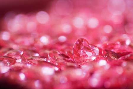 Molti piccoli cuori di cristallo rossi con sfondo bokeh. Scheda romantica a San Valentino.