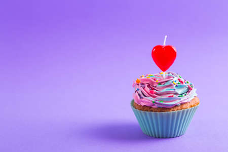 Festive creamy cupcake with sprinkles and candle in form of red heart on purple background. Romantic cake for Valentine's day