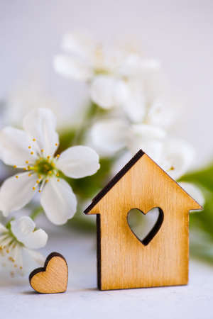 Wooden house with hole in form of heart surrounded by white flowering apricot branches on light background. Spring composition. Stock Photo