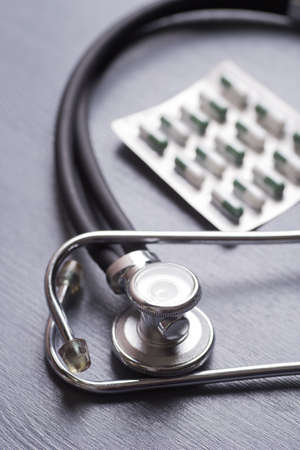 Closeup stethoscope near capsules in blister pack on gray table.