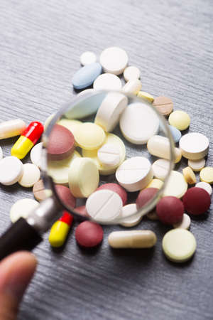 Colorful different capsules and pills under magnifying glass on gray background. Concept of medical research.