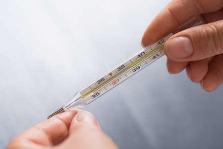 Mãos que guardam o termômetro de mercúrio que mostra a temperatura febrile no fundo cinzento. Conceito de febre.