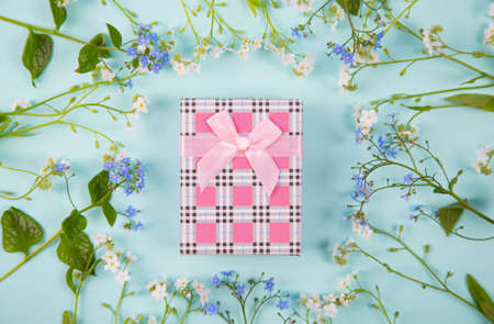 Pink gift box surrounded with blue and white little flowers on light mint background. Spring present with flower frame. Stock Photo