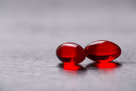 Closeup two red transparent capsules on gray background. Stock Photo