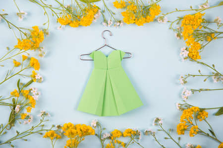 Green paper origami dress on hanger surrounded with yellow and white little flowers on light mint background. Tender Mothers Day card. Concept of spring fashion.