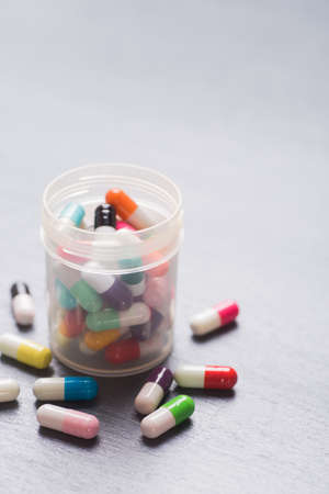 Diversity of colorful different capsules in open transparent jar on gray background. Stock Photo